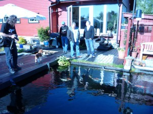 People standing around a koi pond in Norway discussing filtration